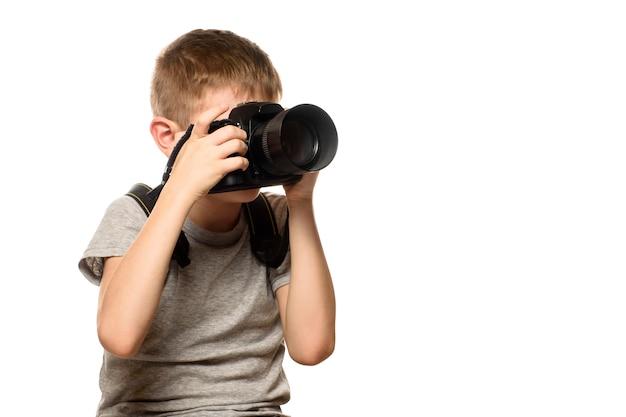 Le garçon prend des photos avec l'appareil photo.