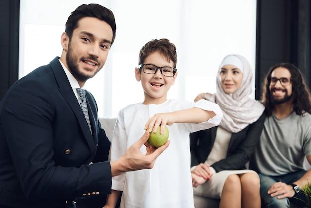 Le garçon prend la pomme chez le psychothérapeute et souriant.