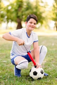 Garçon prépare son football pour un nouveau match