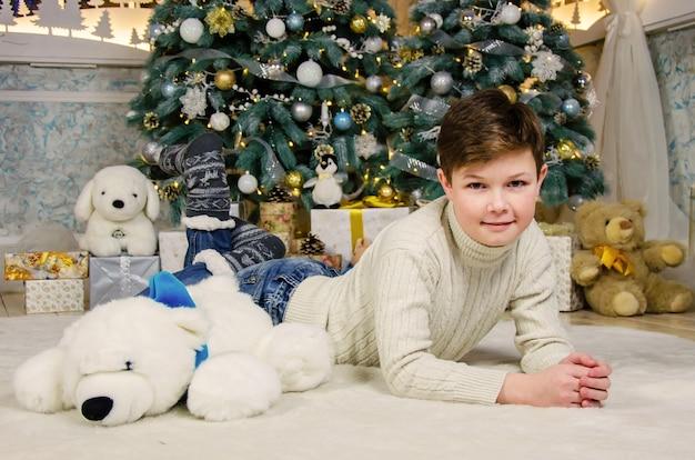 Garçon près de l'arbre de noël à noël avec des jouets