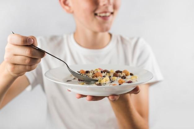 Un garçon prêt à avoir des flocons d'avoine avec une cuillère sur fond blanc