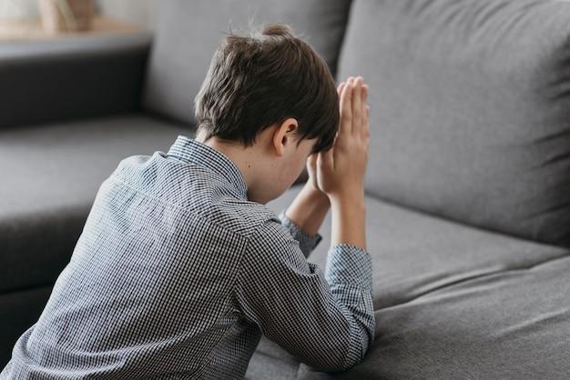Garçon priant sur le canapé à la maison
