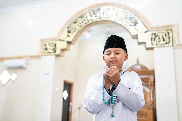 Garçon priant dieu avec le bras ouvert