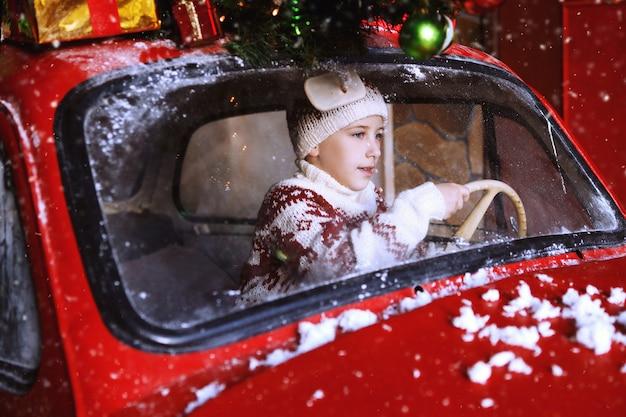 Un garçon en pulls tricotés et un bonnet à pompon avec des cerfs sont assis dans la voiture rouge du nouvel an et sont heureux de l'avènement de noël. enfant s'amusant à l'heure de la nativité. concept de vacances de noël.