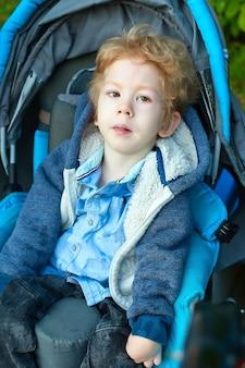 Garçon de quatre ans atteint de paralysie cérébrale assis dans le siège auto.