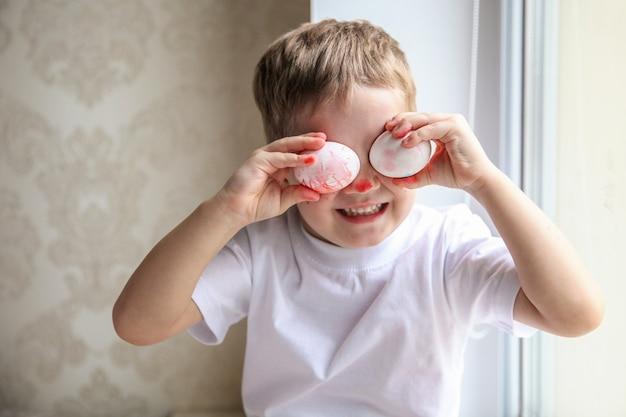 Un garçon de quatre ans vêtu d'un t-shirt blanc et d'un nez peint s'amuse à essayer des œufs de pâques sur ses yeux.