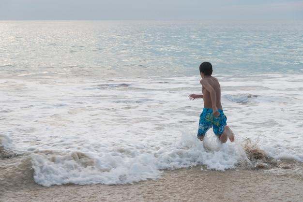 Garçon qui court dans les vagues sur la plage, ixtapa, guerrero, mexique