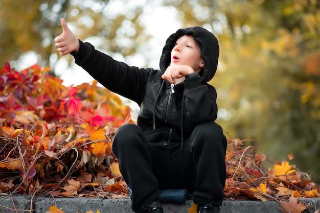 Un garçon qui est assis dans un magnifique parc d'automne, montre le côté avec sa main.