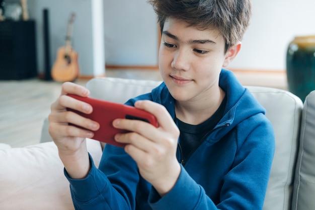 Le garçon qui joue à des jeux en ligne sur son téléphone portable