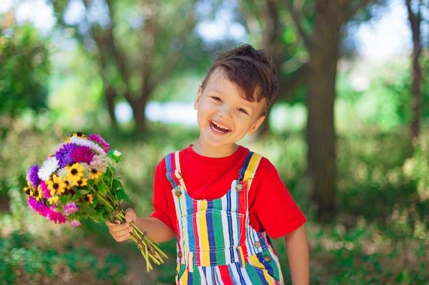 Garçon qui rit avec un bouquet de fleurs sauvages dans ses mains dans le contexte de la fête des mères nature