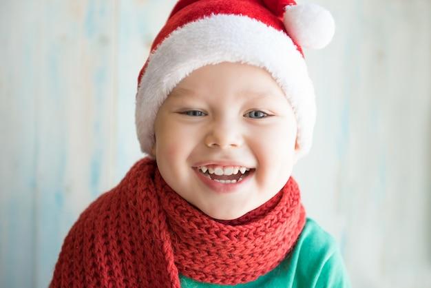 Garçon qui rit dans un chapeau de noël et une écharpe rouge