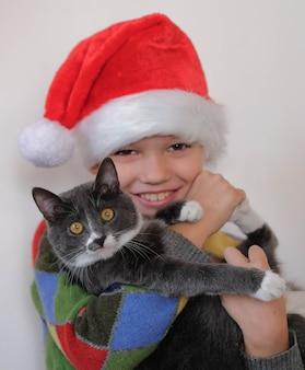 Garçon qui rit tient un chat dans ses bras. attributs de noël.