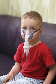 Un garçon de race blanche inhale des couples contenant des médicaments pour arrêter la toux.