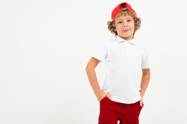 Garçon de race blanche en t-shirt blanc, bonnet rouge, short rouge sourit isolé sur blanc