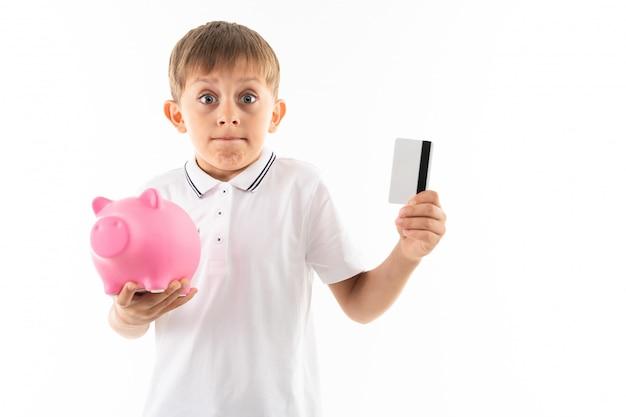 Garçon de race blanche avec tirelire et carte de crédit avec maquette sur blanc