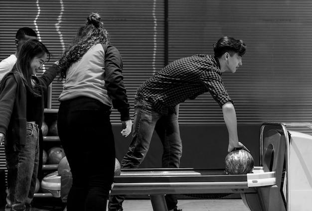Garçon ramassant la boule de bowling rouge