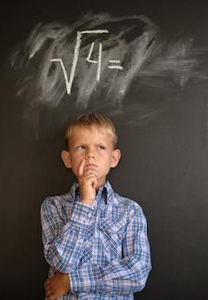 Garçon réfléchit à la solution de problèmes mathématiques
