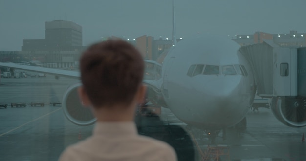 Garçon regardant l'avion par la fenêtre de l'aéroport