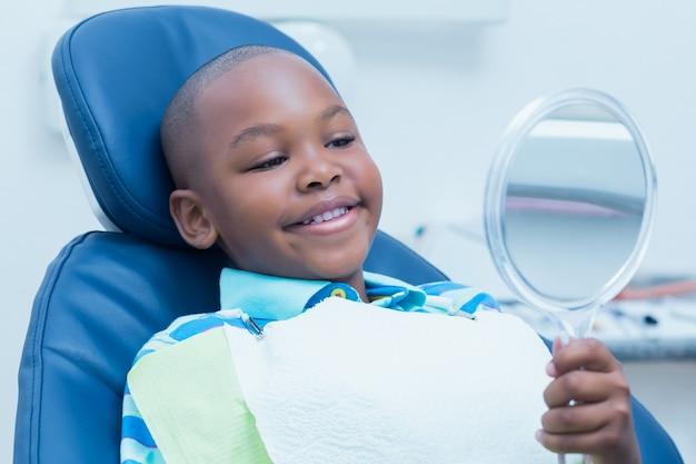 Garçon regardant miroir dans la chaise des dentistes