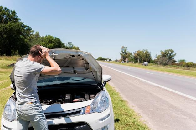 Garçon regardant une voiture en panne