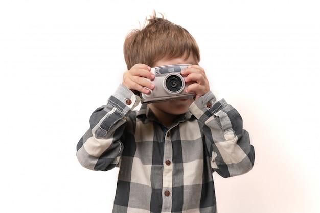 Le garçon regarde la caméra et prend des photos