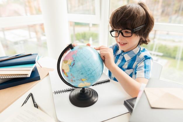 Le garçon regarde le globe à la maison.