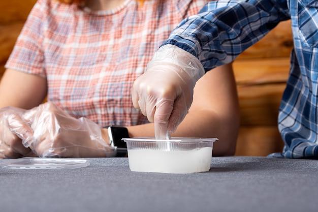 Garçon en remuant un mélange avec une cuillère-mesure dans un récipient avec des éléments chimiques à la maison