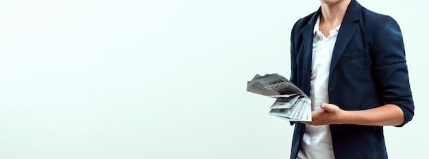 Un garçon riche sur fond clair tient un paquet de dollars dans ses mains. éducation financière.