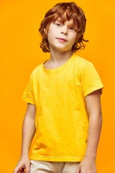 Garçon rousse dans un t-shirt jaune posant
