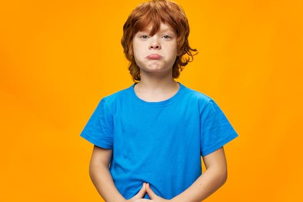 Garçon rousse l'enfant offensé a fait la moue des lèvres t-shirt bleu jaune