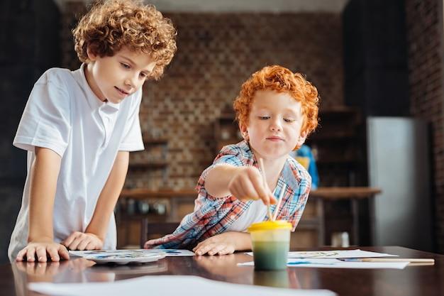 Garçon rousse mignon lave son pinceau tout en travaillant sur un nouveau chef-d'œuvre tandis que son frère aîné se tient à côté de lui et regarde sa peinture.
