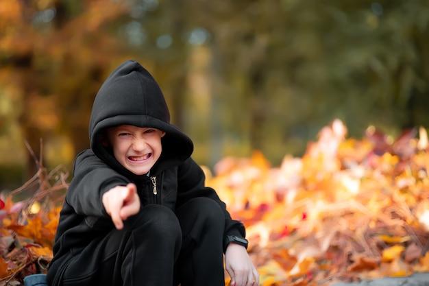 Un garçon rusé dans une veste à capuche noire est assis sur le trottoir et sourit