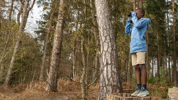Garçon s'amusant dans les bois