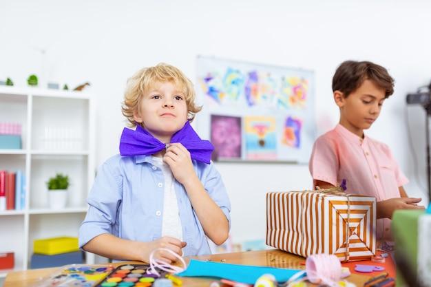 Garçon s'amusant. drôle de garçon aux yeux noirs s'amusant tout en mettant un nœud en papier sur son cou à une belle leçon d'art
