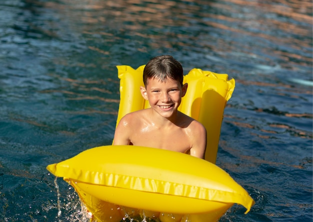 Garçon s'amusant à la piscine avec flotteur de piscine
