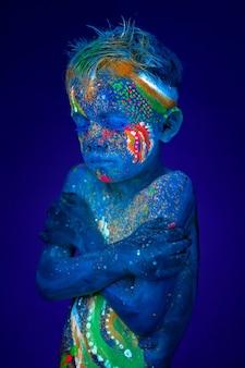 Le garçon s'embrasse, il a très froid. posant en lumière ultraviolette uv