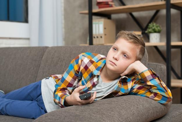 Garçon s'ennuie sur le canapé