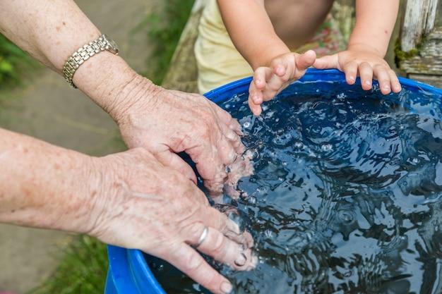 Un garçon et sa grand-mère se lavant les mains dans le tonneau d'eau