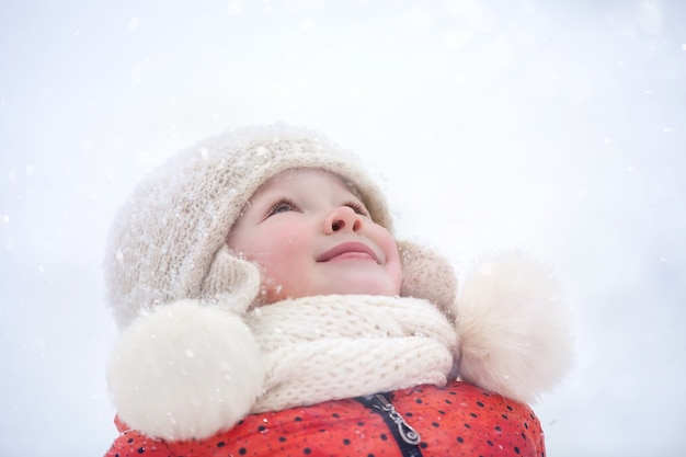 Un garçon et sa sœur cadette marchent dans le parc un jour d'hiver enneigé