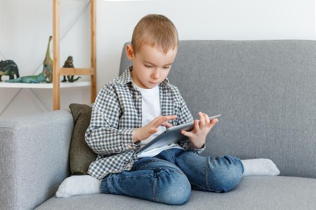 Garçon sans contrôle parental perdre du temps à jouer à des jeux kid s'amusant avec une tablette