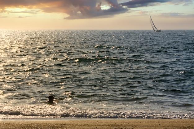 Garçon se baignant dans la mer au coucher du soleil et un voilier naviguant en arrière-plan.