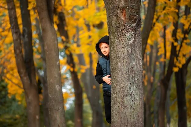 Garçon se cachant derrière les arbres d'automne dans le parc.