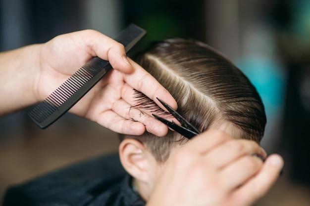 Le garçon se fait couper les cheveux par des ciseaux dans un salon de coiffure