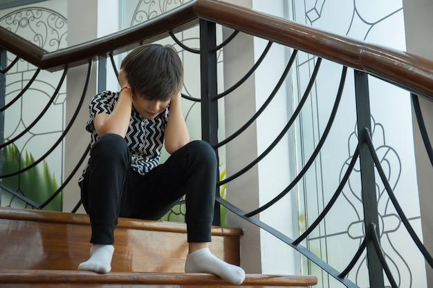 Le garçon se ferme les oreilles entre les parents se querellent combats. arrêtez le concept de violence.