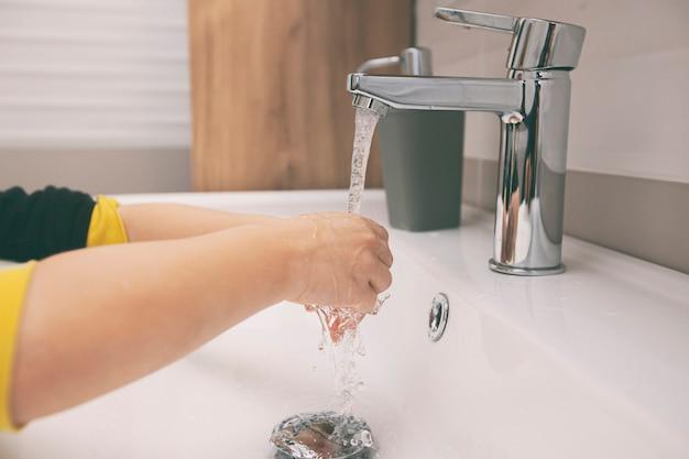 Le garçon se lave les mains avec du savon sous l'eau