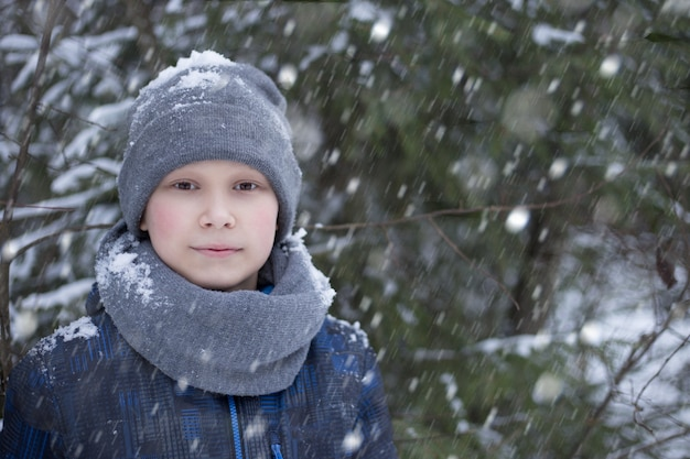 Un garçon se promène dans la forêt en hiver