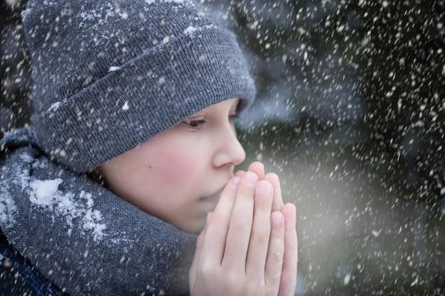 Un garçon se réchauffe les mains du froid en hiver