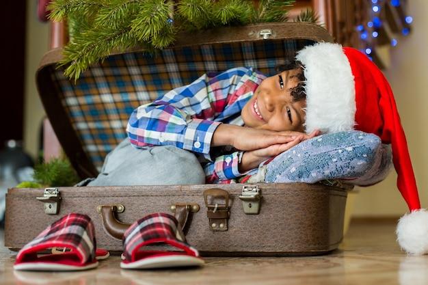 Garçon se réveillant dans une valise. le sourire matinal du petit père noël. le plus beau matin de l'année. hâte de voir les cadeaux.