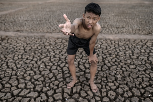 Le garçon se tenait plié sur ses genoux et a fait une marque pour demander la pluie, le réchauffement climatique et la crise de l'eau.