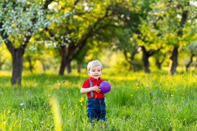 Un garçon se tient dans une clairière et joue avec un ballon